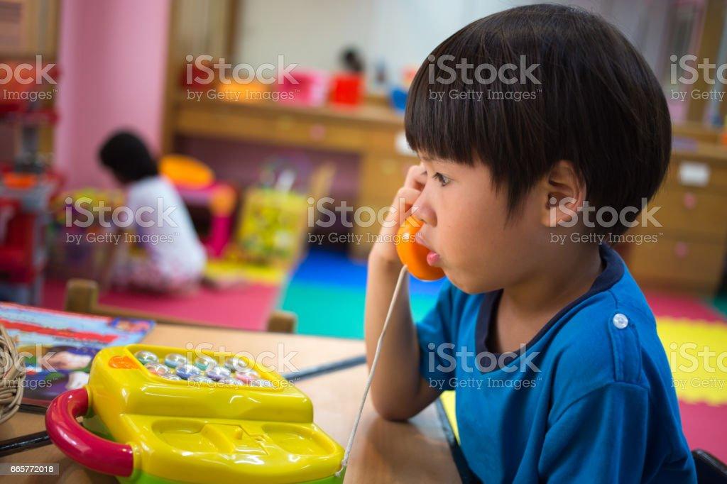 4 Jahre alten asiatischen Jungen spielen abholen Spielzeug Telefon im Spielzimmer – Foto