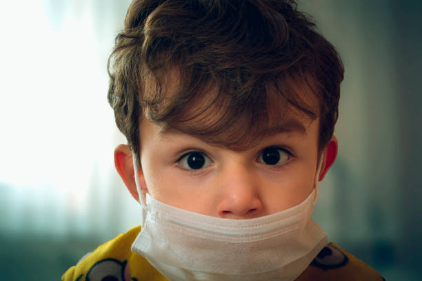 3 years old baby wearing surgical mask peering anxiously at the camera stock photo