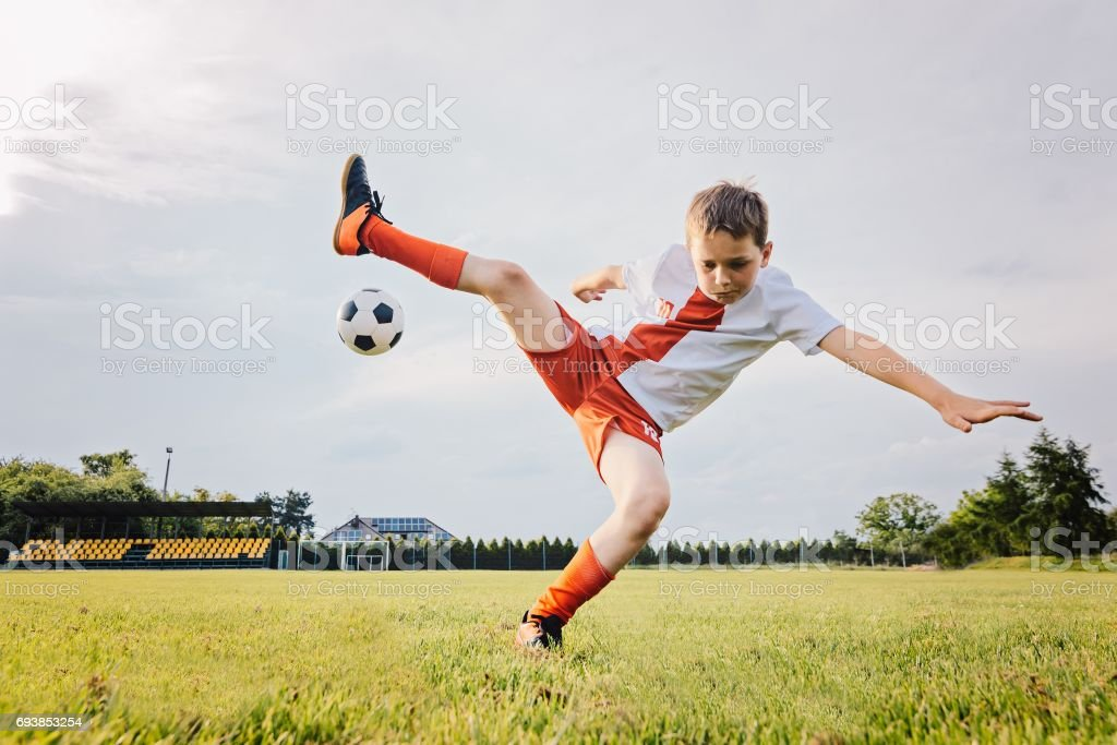 8 years old boy child playing football and rolls over stock photo