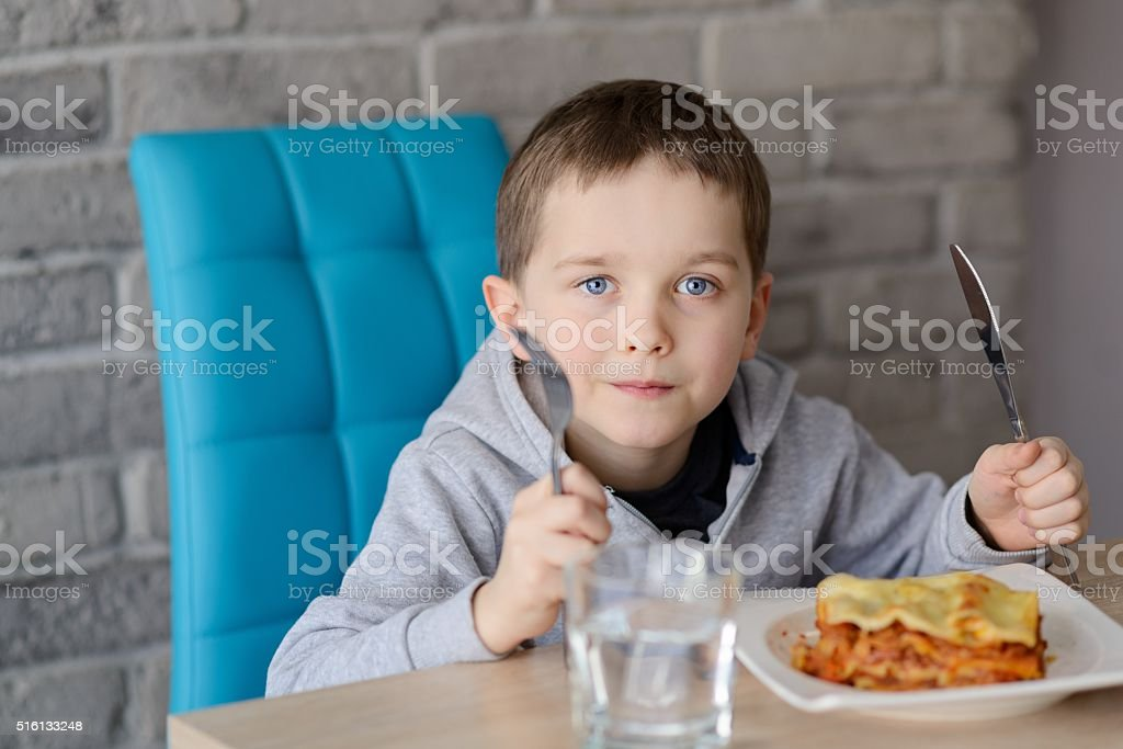 Pranzo Per Bambini 7 Anni : 7 anni ragazzo mangia lasagne in sala da pranzo fotografie stock e