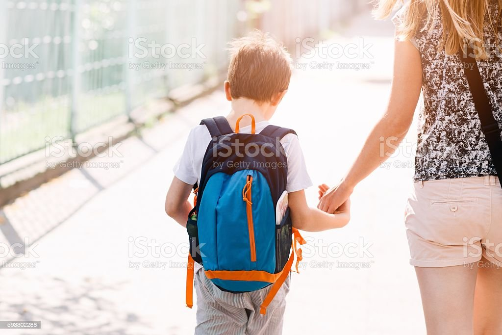 7 years old boy going to school with his mother - Photo
