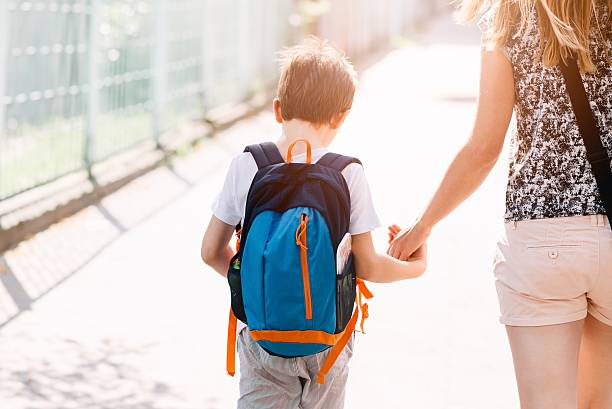 7 years old boy going to school with his mother - foto de stock
