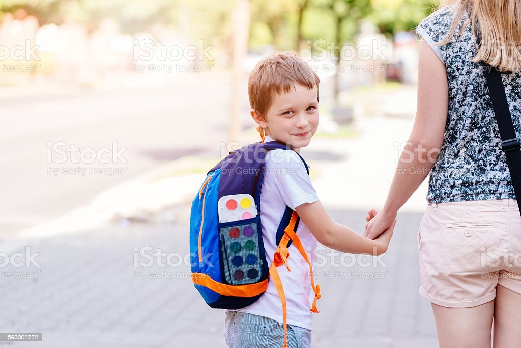 7 years old boy going to school with his mother stock photo