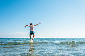 13 years old boy swimming and relaxation in the sea waves. Concept of family summer vacation