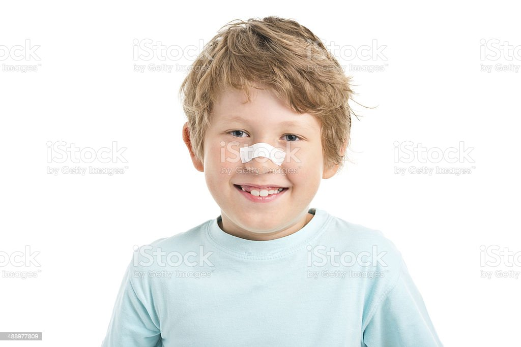 8 years old boy with a plaster on his forehead stock photo