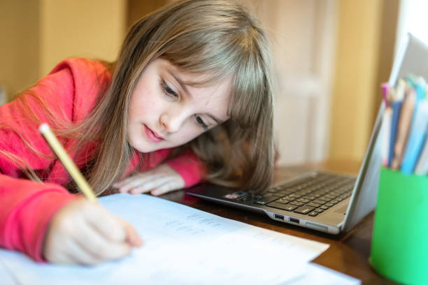 8 years old child girl studying from home stock photo