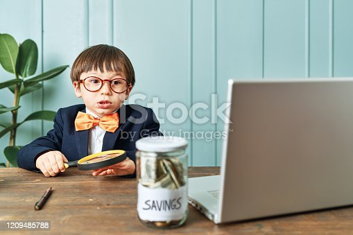 istock 2-3 years old child wearing a suit like a businessman and he work in his office table. 1209485788