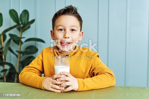 6-7 years old cute child drinking milk on table. He knows that he needs to drink milk for healthy bones. He loves milk.