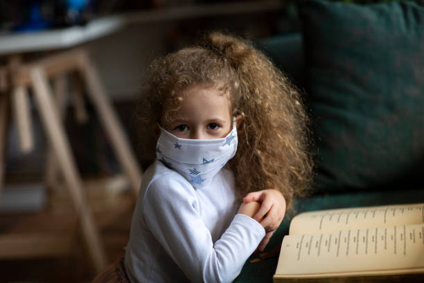 5-6 years old cute child wearing surgical mask and reading book at home. stock photo
