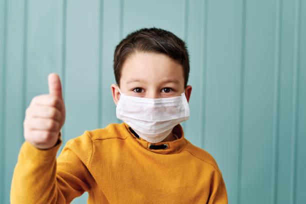 enfant mignon de 6-7 ans utilisant le masque chirurgical. - masque enfant photos et images de collection