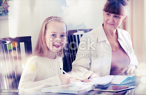 istock 10 years old girl and her teacher. Little girl study during her private lesson. 656773238
