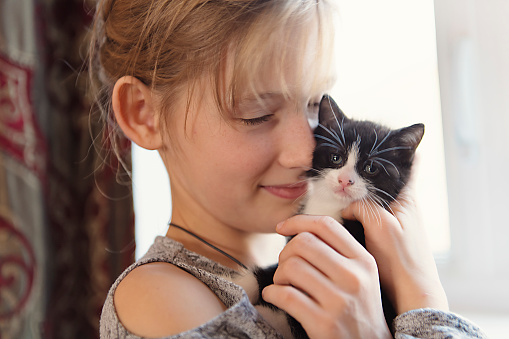 istock 10 years old girl with kitten at home 1080240094