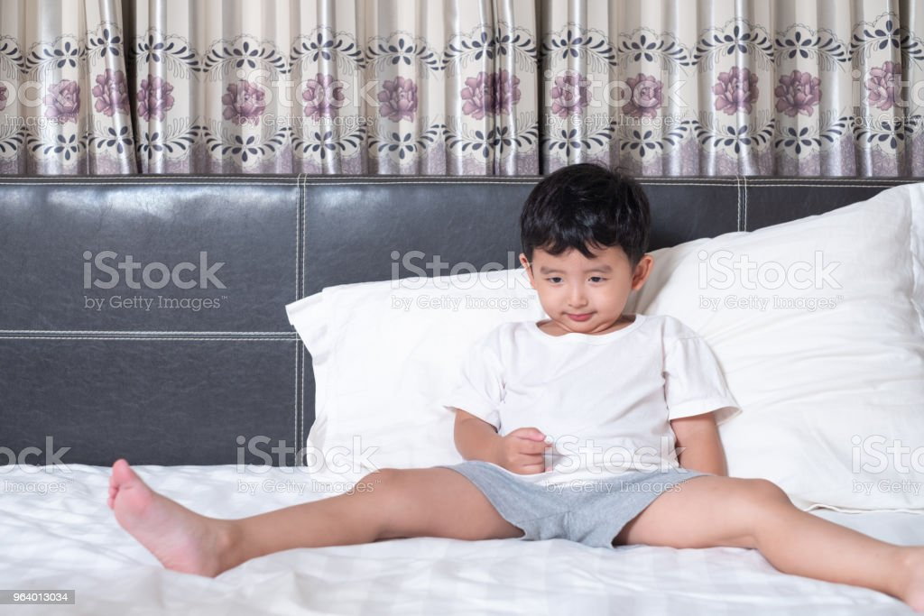 3 years old little cute Asian boy at home on the bed, kid lying playing and smiling on white bed with pillow and blanket, with copy space. - Royalty-free Asia Stock Photo