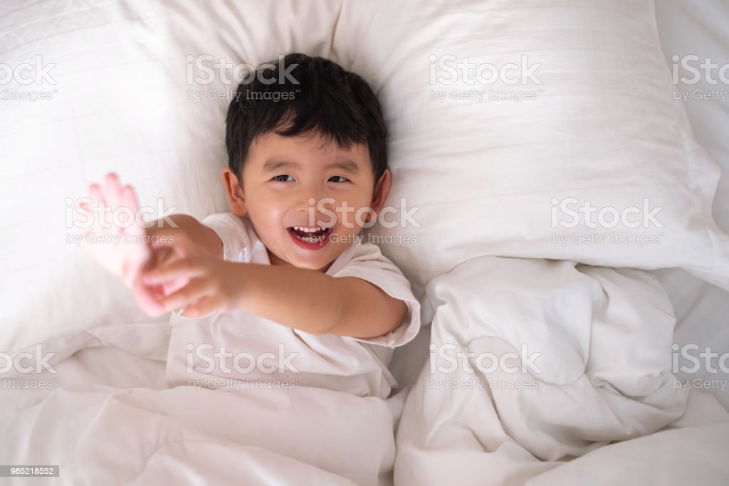 3 years old little cute Asian boy at home on the bed, kid lying playing and smiling on white bed with pillow and blanket, top view with copy space. zbiór zdjęć royalty-free