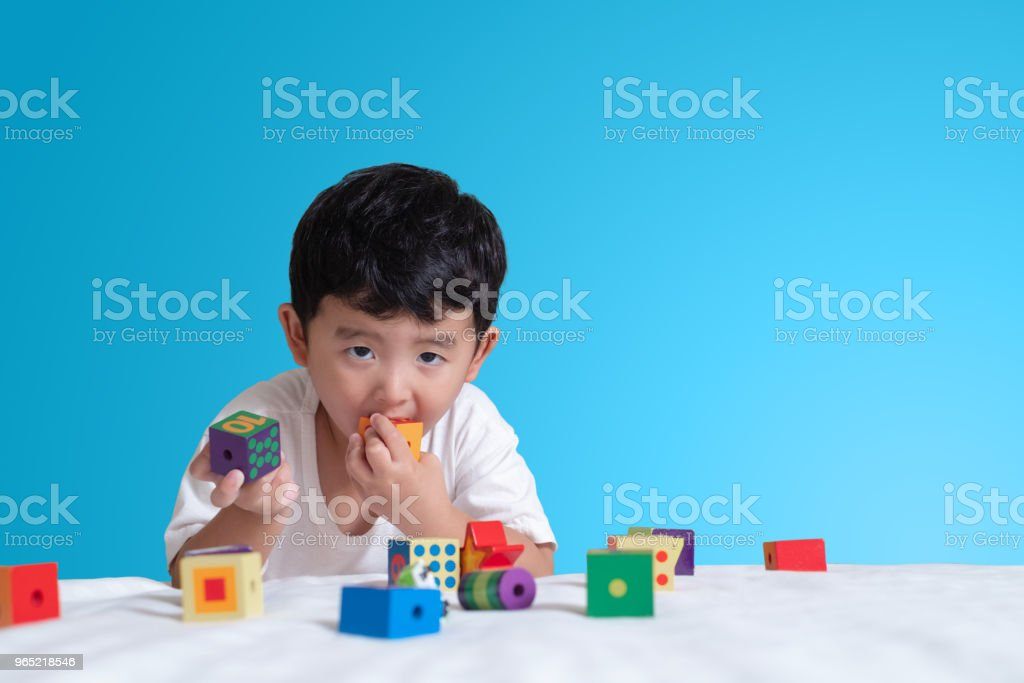 3 years old little cute Asian boy play toy or square block puzzle at home on the bed, kid lying learn by playing block shape or pieces, education and healthy concept idea. zbiór zdjęć royalty-free