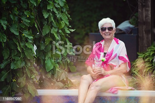 84 years old senior woman in the pool enjoying the sun and a cocktail