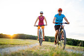 low angle view athletic sporty fit happy smiling  woman and man couple friends in their fourties cycling with their electric mountain bicycles on gravel path through grassland rural landscape on sunny summer afternoon sunset