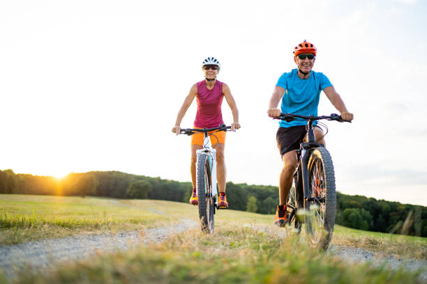 coppia sportiva di 40-50 anni in bicicletta su mountain bike elettriche in ambiente rurale - ciclismo foto e immagini stock