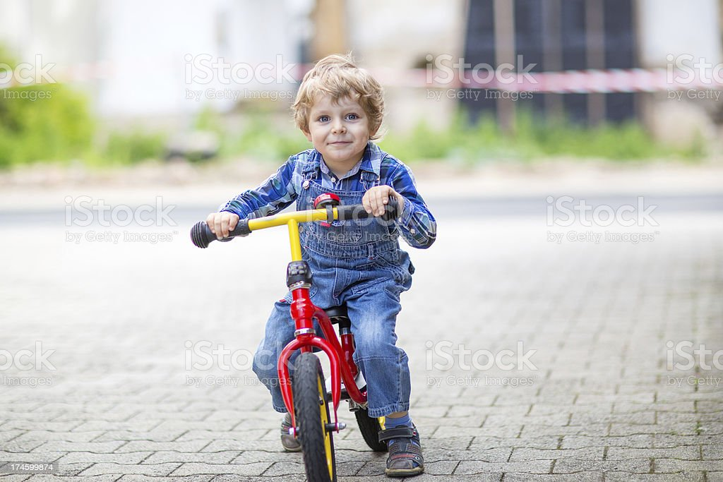 3 years old toddler riding on his first bike stock photo