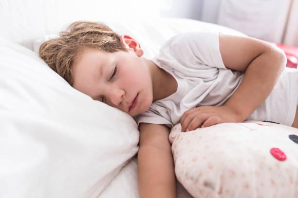 3 años niño pequeño durmiendo la siesta en la cama - foto de stock
