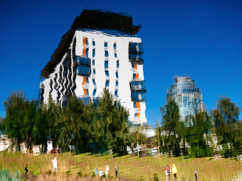 Yekaterinburg, Russia, August 27, 2020: the Kandinsky residential building is reflected in the river. Luxury real estate in the city center. Beautiful city embankment
