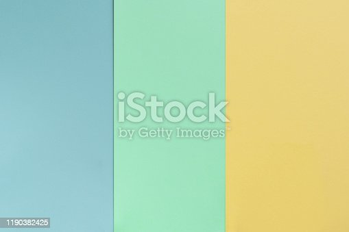 Yelllow green blue color paper background. Geometric flat composition. Empty space on monochrome cardboard