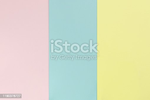 Yelllow pink blue color paper background. Geometric flat composition. Empty space on monochrome cardboard