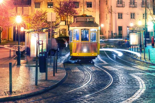 yellow 28 tram in alfama at night, lisbon, portugal - eletrico lisboa imagens e fotografias de stock
