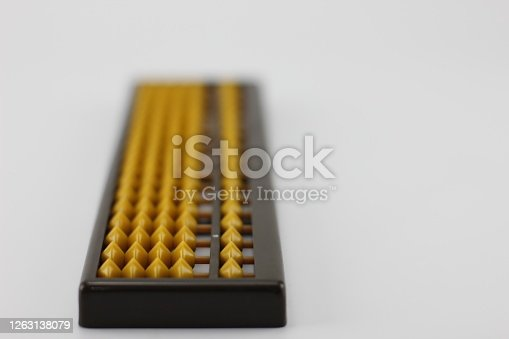 Yellow abacus  Is plastic placed on a white background.