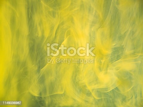 Yellow acrylic clouds swirling under water, abstract background. Close up view. Blurred background. Selective soft focus. Yellow paint dissolving into water. Background for abstract wallpapers