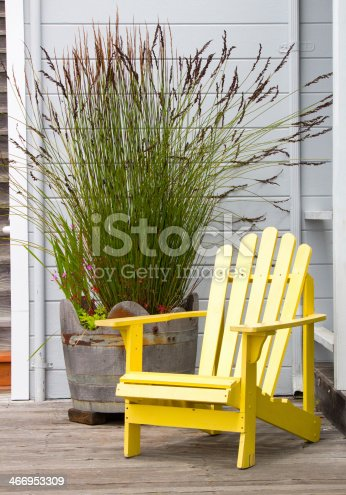 A nice yellow adirondack chair on a a wooden deck. Nice inviting spot to relax.