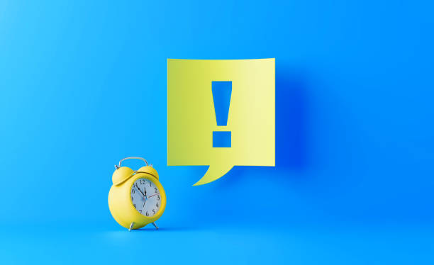 Yellow Alarm Clock And Yellow Speech Bubble With Exclamation Point On Blue Background Yellow alarm clock with a yellow speech bubble and exclamation point on blue background. Start writes on the speech bubble. Horizontal composition with copy space. clock hand stock pictures, royalty-free photos & images