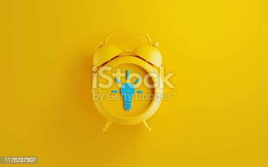 Yellow alarm clock on yellow background. There is a blue lightbulb icon on the clock. Reminder concept. Horizontal composition with copy space.