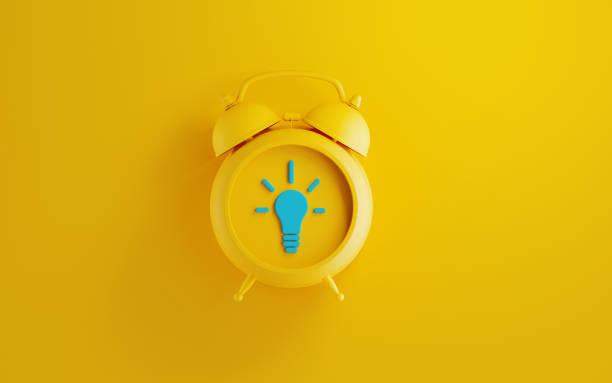 Yellow Alarm Clock on Yellow Background stock photo