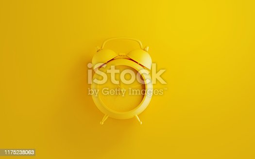 Yellow alarm clock on yellow background. Reminder concept. Horizontal composition with copy space.