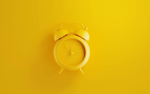 Gelber Wecker auf gelbem Hintergrund – Foto