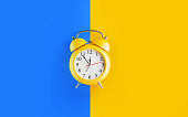 Yellow alarm clock over bright blue and yellow background. Reminder concept. Horizontal composition with selective focus and copy space.