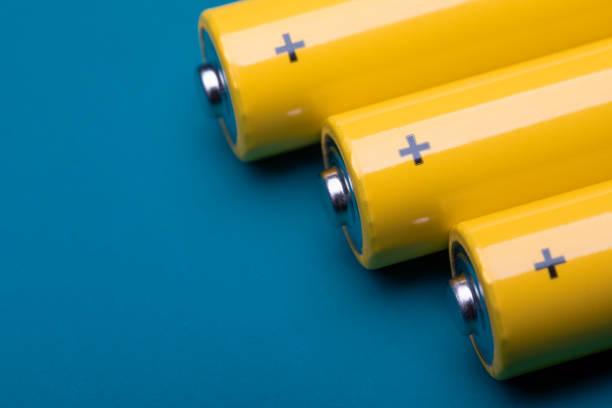 Yellow alkaline batteries on blue background stock photo