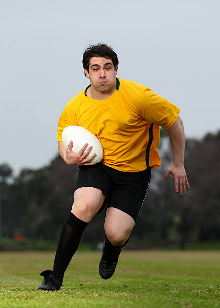 Yellow and black male rugby player runs with ball stock photo