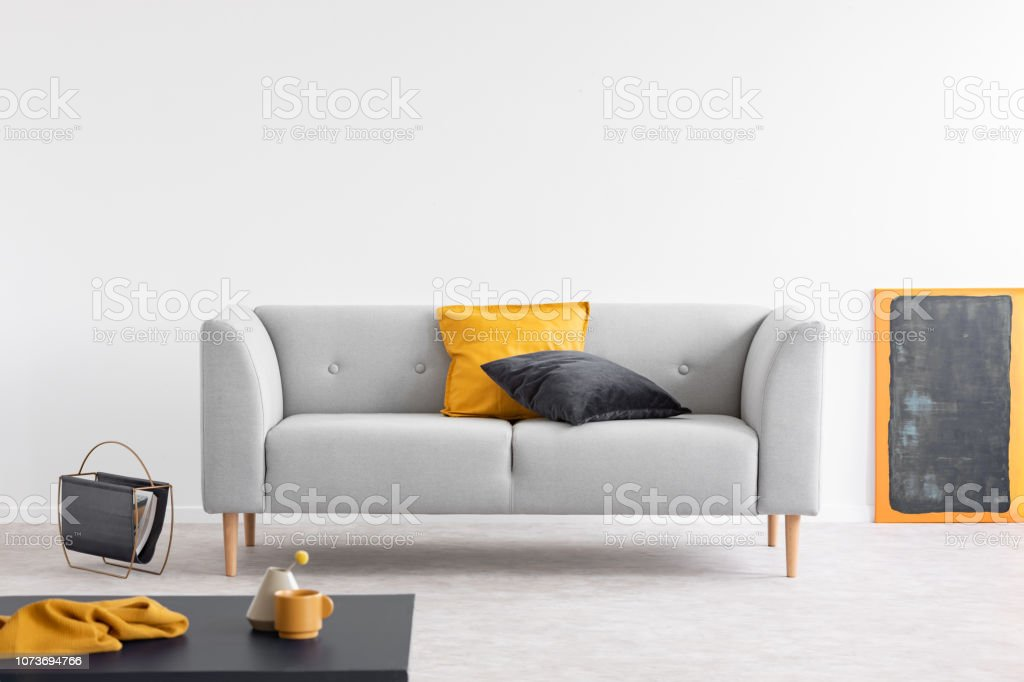 Yellow And Black Pillows On Grey Settee In Spacious Living Room Interior With Blackboard Orange Frame Magazine Rack The Floor Stock Photo Download Image Now Istock