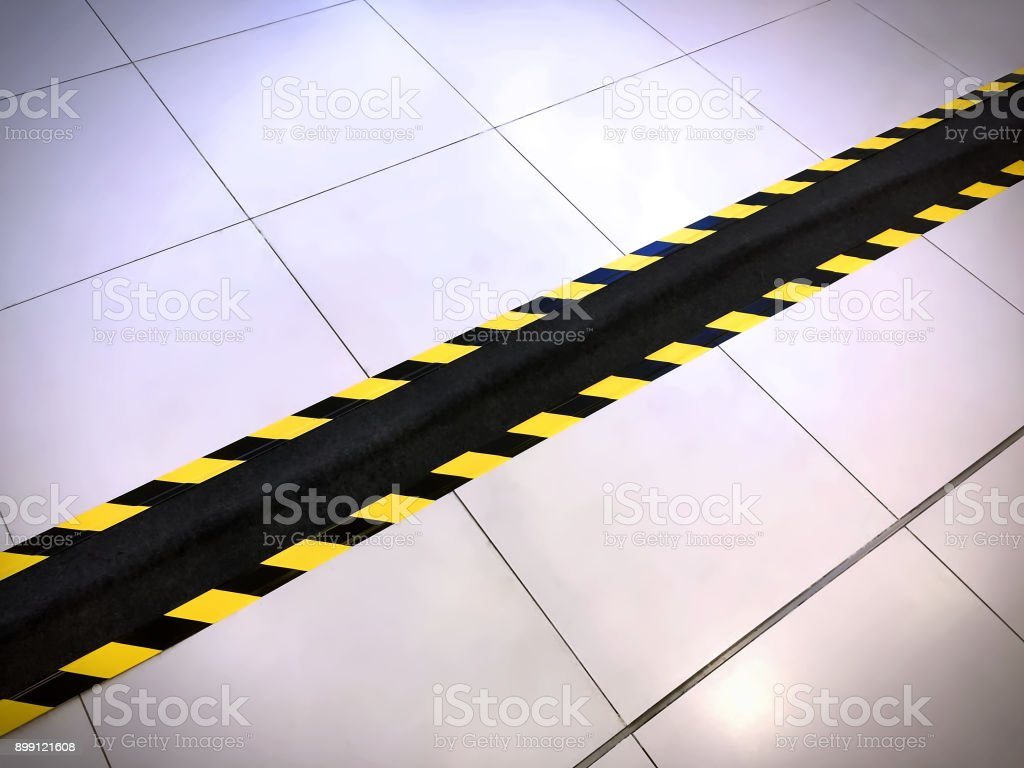 Yellow and Black Warning Stripes on Black Tape Covering Electrical Wire Duct on the Floor stock photo
