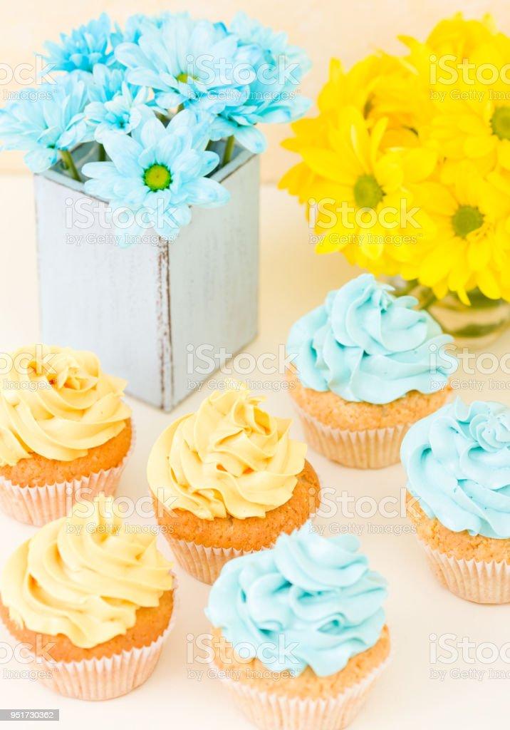 Crisântemo amarelo e azul no vaso chique gasto com cupcakes decorados com creme macio. Área do Copyscape - Foto de stock de Alimentação Não-saudável royalty-free