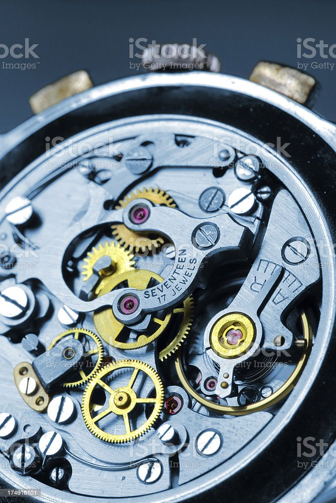 Yellow and blue gears inside wrist watch stock photo
