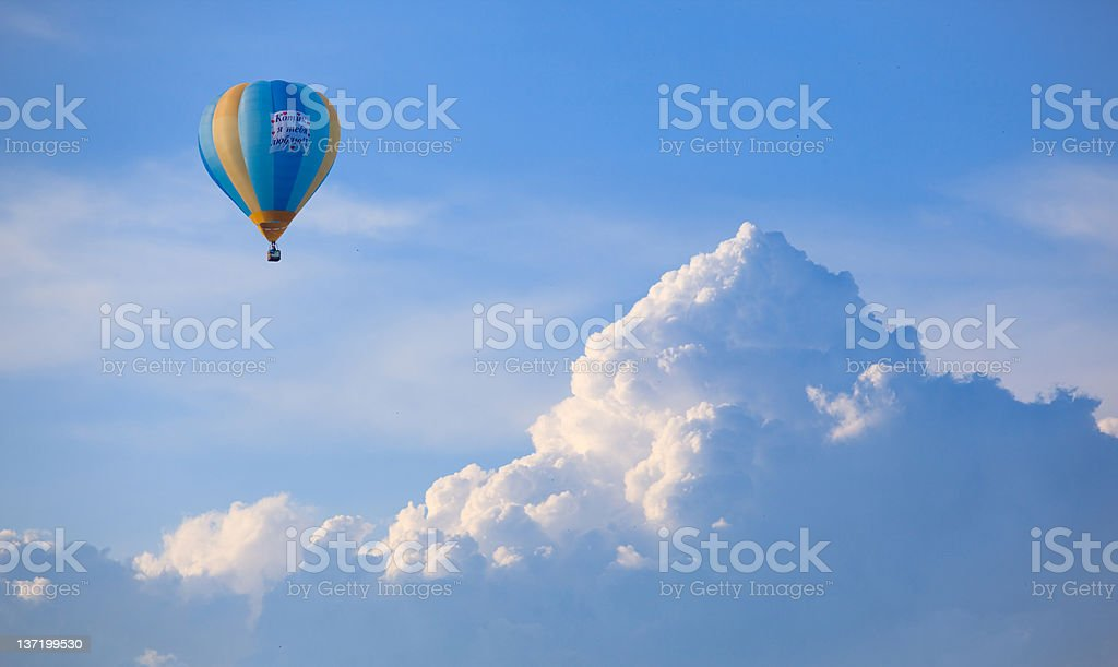 Yellow and blue hot air balloon floating in the cloudy sky royalty-free stock photo