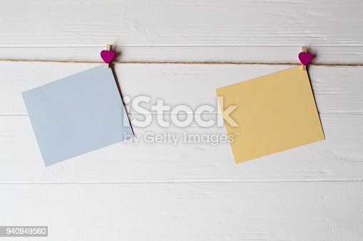 istock Yellow and blue memo sheets fastened with a decorative pins on a white wooden board. 940949560