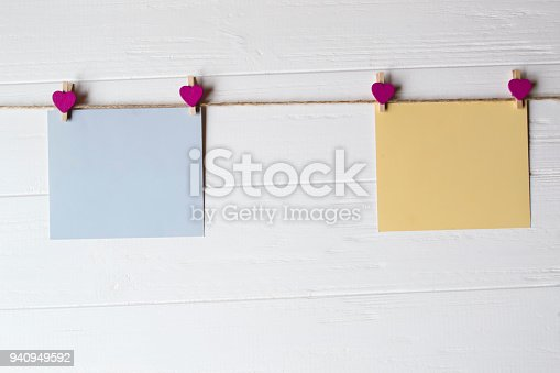 istock Yellow and blue memo sheets fastened with a decorative pins on a white wooden board. 940949592