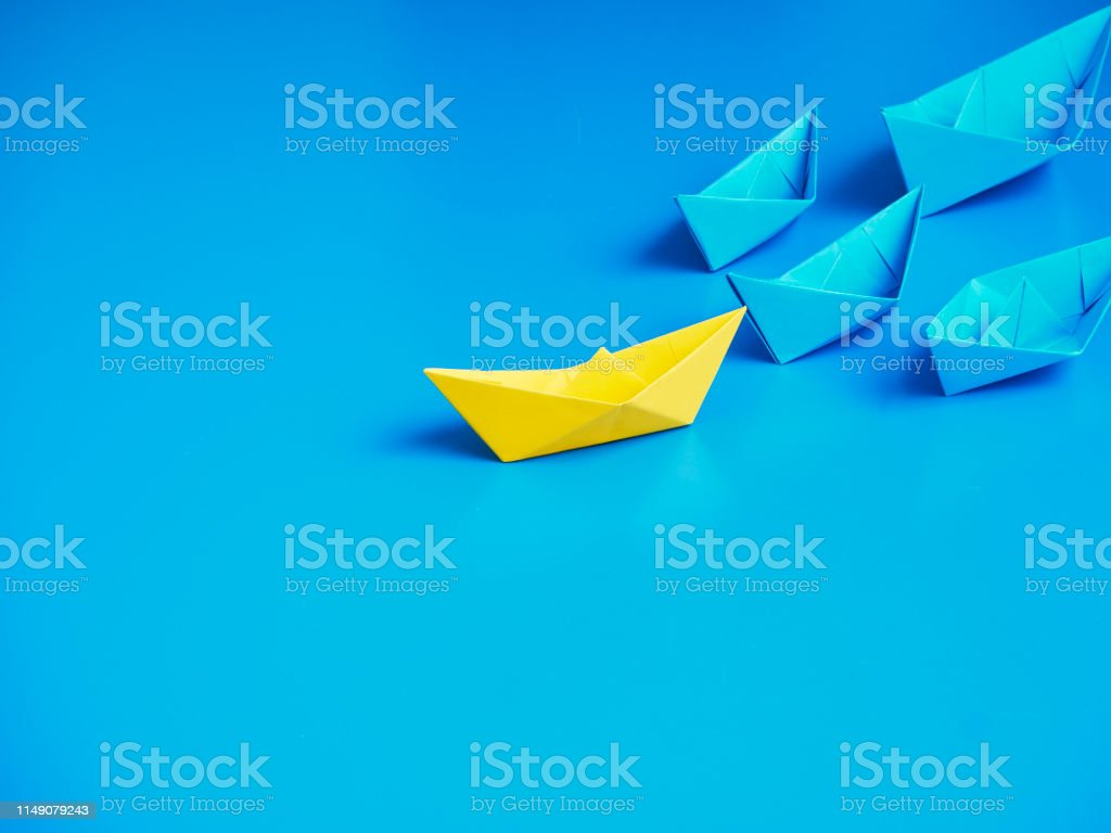 Set of origami boats. One Yellow paper boat leading among Blue ships...