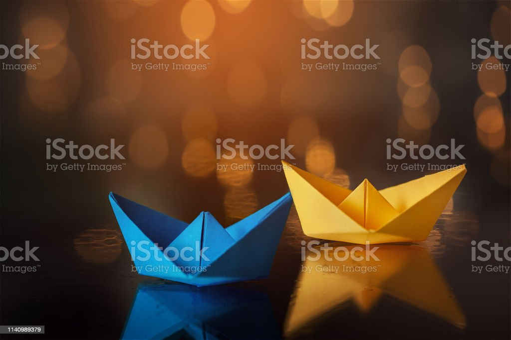 Blue and yellow paper ship ships on dark background.