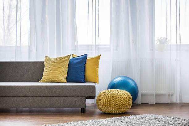 yellow and blue pillows on couch - mädchenraum vorhänge stock-fotos und bilder