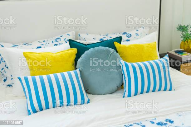 Yellow and blue pillows on white bed at home picture id1174254557?b=1&k=6&m=1174254557&s=612x612&h=pqxnk ltadmcrtbodvbrfl8p0iwixk70d 2h2n1r7gc=